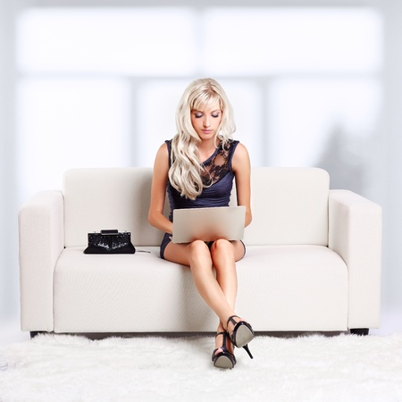full-length portrait of beautiful young blond woman relaxing on couch with laptop photo