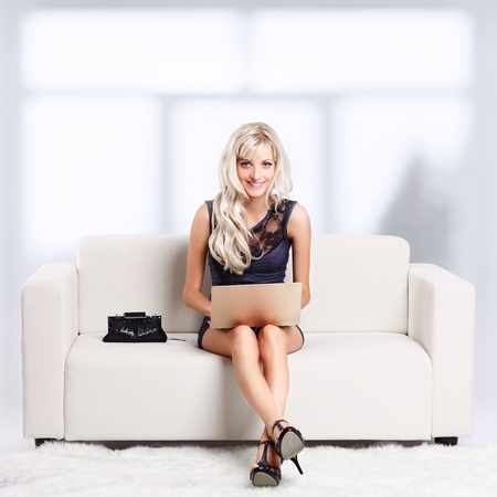 full-length portrait of beautiful young blond woman relaxing on couch with laptop Stock Photo - 12106019