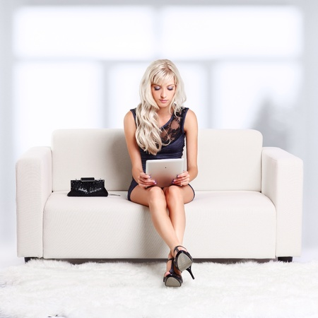 full-length portrait of beautiful young blond woman on couch with tablet pc Stock Photo - 12105990