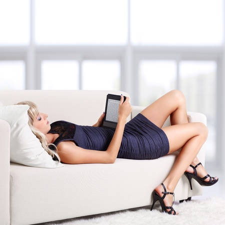 electronic book: full-length portrait of beautiful young blond woman on couch and reading e-book