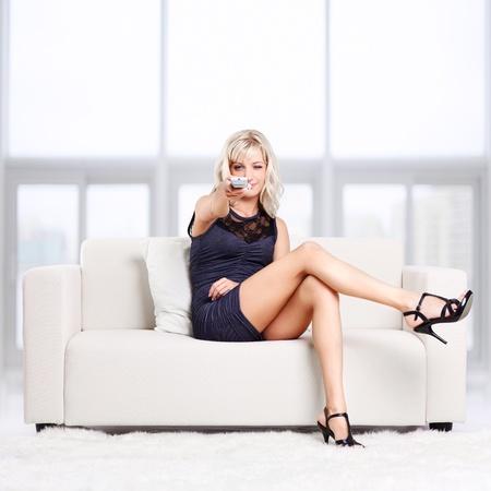 ver tv: retrato de cuerpo entero de la hermosa joven rubia sentada en el sofá con mando a distancia