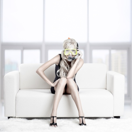 young blond woman in scuba mask on couch with white furs on floor Stock Photo - 12106066
