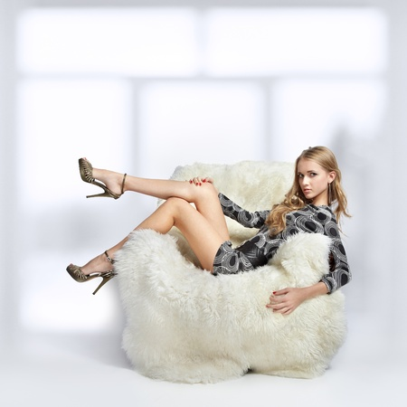 portrait of beautiful blonde blue-eyed girl sitting in big furry arm-chair photo