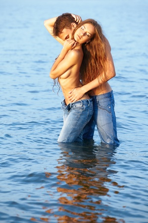 topless jeans: outdoor portrait of beautiful romantic couple of topless girl and muscular guy in jeans posing in sea waters Stock Photo