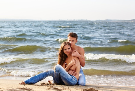 outdoor portrait of beautiful romantic couple of girl and muscular guy in jeans on beach