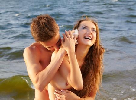 Ritratto di ragazzo outdoor muscolare mettere shell bella all'orecchio ridere ragazza topless 's