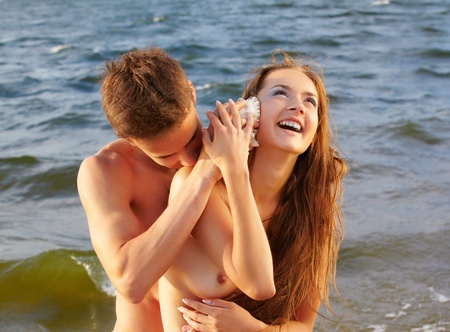 outdoor portrait of muscular guy putting shell to beautiful laughing topless girl s ear photo