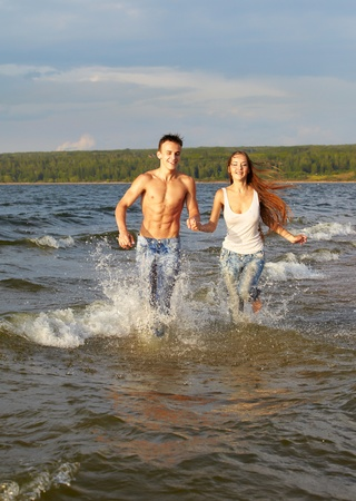outdoor portrait of beautiful romantic couple of slim girl and muscular guy in jeans running in coastal strip photo
