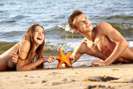 outdoor portrait of beautiful romantic couple of topless girl and muscular guy in jeans laying face to face with asteroid on beach photo