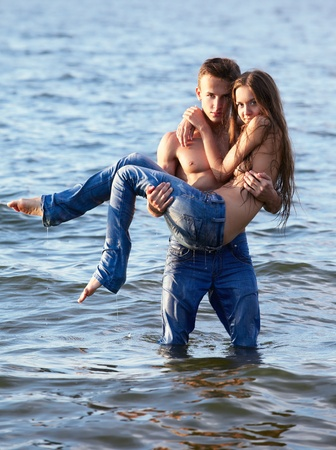 outdoor portrait of beautiful romantic couple of topless girl and muscular guy in jeans posing in sea waters. guy holds girl on hands photo