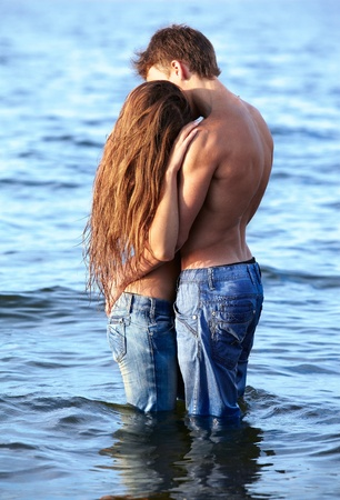 outdoor portrait of beautiful romantic couple of topless girl and muscular guy in jeans posing in sea waters photo
