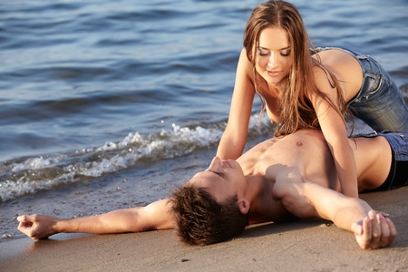 outdoor portrait of beautiful romantic couple of topless girl and muscular guy in jeans on beach photo