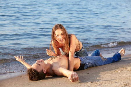 outdoor portrait of beautiful romantic couple of topless girl and muscular guy in jeans on beach. girl drops sand on guys chest photo