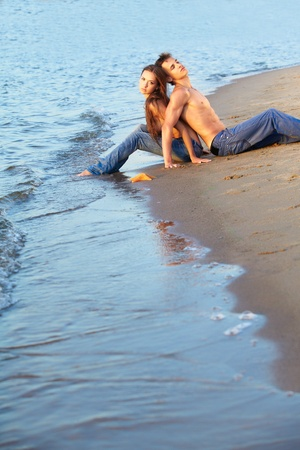 outdoor portrait of beautiful romantic couple of topless girl and muscular guy in jeans sitting back to back on beach photo