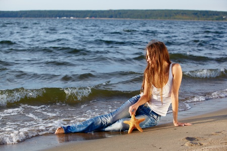 outdoor portrait of beautiful girl in jeans posing on beach with asteroid Stock Photo - 12341774