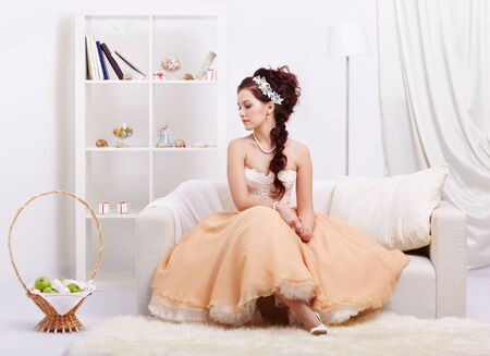 portrait of young beautiful retro woman in skirt with petticoat and corset posing in vintage interior photo