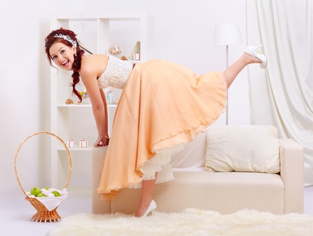 portrait of young beautiful retro woman in skirt with petticoat and corset posing in vintage interior standin one one leg and laughing photo