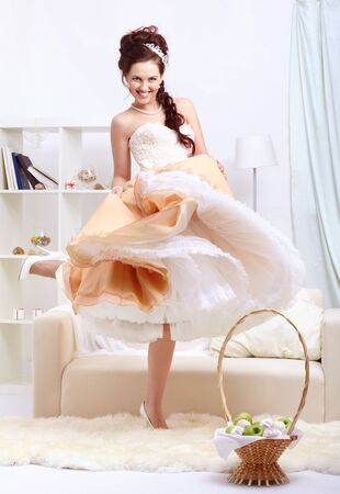 Portrait of young beautiful dancing retro woman in vintage skirt with petticoat and corset on gray photo
