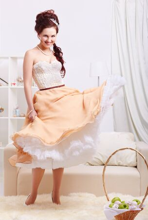 portrait of young beautiful retro woman in vintage skirt with petticoat and corset on gray photo