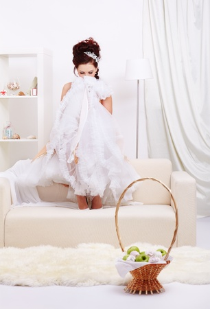 portrait of young beautiful retro woman sitting on sofa in interior and hiding her face behind vintage skirt petticoat Stock Photo - 12341848