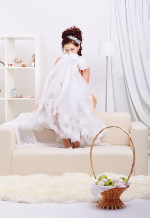 portrait of young beautiful retro woman sitting on sofa in interior and hiding her face behind vintage skirt petticoat photo