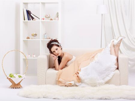 portrait of young beautiful retro woman in skirt with petticoat and corset lying on sofa in vintage flat Stock Photo - 12341845