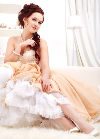 portrait of young beautiful retro woman in skirt with petticoat and corset posing in vintage flat photo
