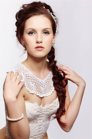 portrait of young beautiful retro woman in vintage corset and accessories on gray photo