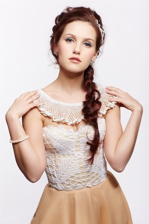 portrait of young beautiful retro woman in vintage corset, skirt and accessories on gray photo