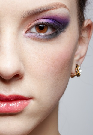 close-up half-face portrait of young beautiful woman with violet eye shadow photo