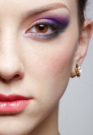 de cerca de media cara retrato de mujer joven hermosa con sombra de ojos violeta
