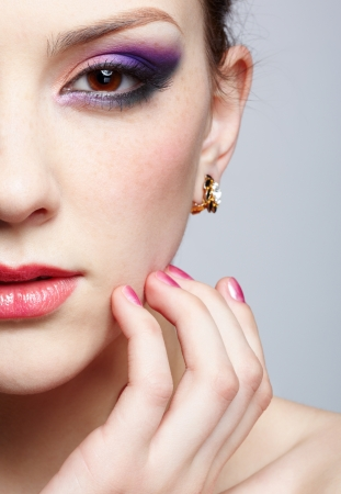 close-up half-face portrait of young beautiful woman with violet eye shadow touching her face with manicured fingers photo