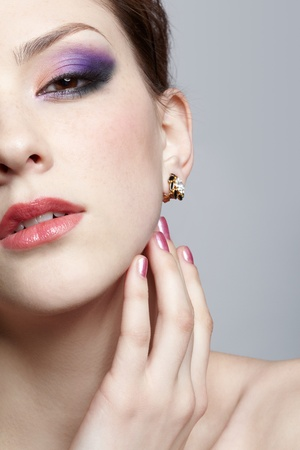 close-up half-face portrait of young beautiful woman touching her face with manicured fingers photo