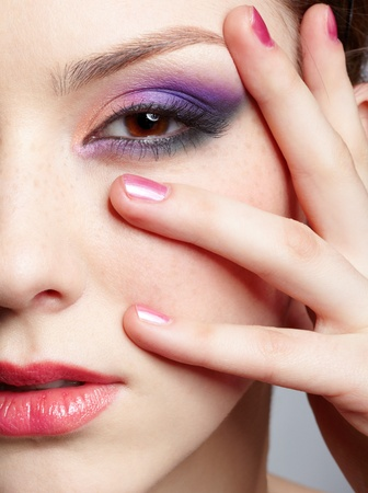 close-up half-face portrait of young beautiful woman with violet eye shadow touching her face with manicured hand photo