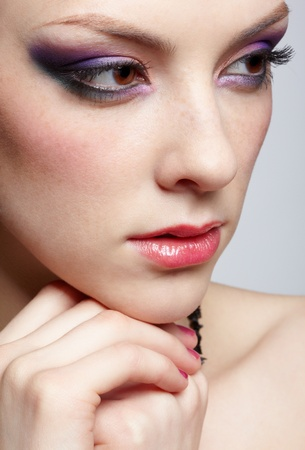 close-up portrait of young beautiful woman with violet eye shadow on gray Stock Photo - 12341946