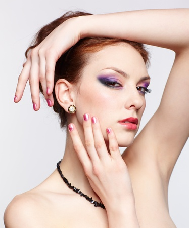 portrait of young beautiful redhead woman in beads and ear-rings touching her face with hands photo