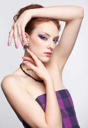 portrait of young beautiful redhead woman in violet dress, beads and ear-rings touching her face with hands photo