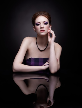 portrait of beautiful young redhead woman at dark mirror table Stock Photo - 12341980