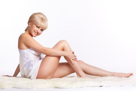 sideview full-length portrait of beautiful young blonde woman in lingerie sitting on white fur carpet photo