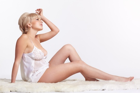 nude girl sitting: sideview full-length portrait of beautiful young blonde woman in lingerie sitting on white fur carpet