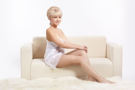 full-length portrait of beautiful young blonde woman in lingerie on white coach photo