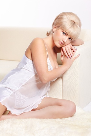 full-length portrait of beautiful young blonde woman in lingerie sitting near white coach Stock Photo - 12341876