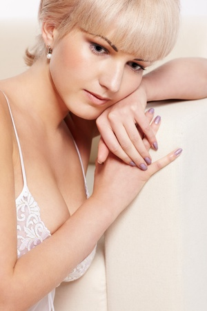 full-length portrait of beautiful young blonde woman in lingerie sitting near white coach photo