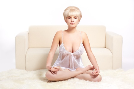 full-length portrait of beautiful young blonde woman in lingerie sitting in yoga lotus pose on white fur carpet photo