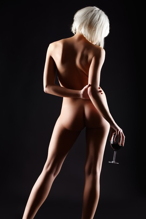 nude woman back: portrait of young blonde woman with beautiful body posing with glass of red wine in hand