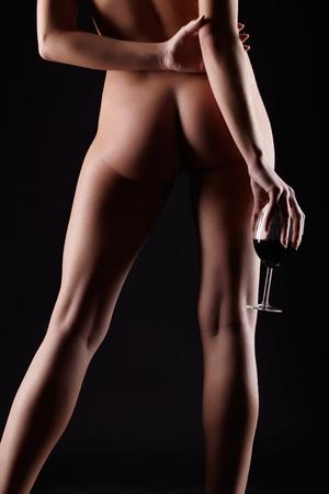 mujer desnuda de espalda: retrato de una mujer joven rubia con hermosas piernas posando con vaso de vino tinto en la mano