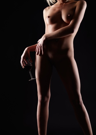 naked silhouette: body part portrait of young woman with beautiful breasts with glass of red wine in hand