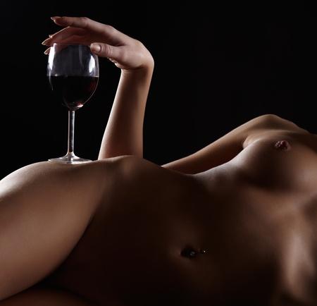 femme se deshabille: portrait partie du corps de la jeune femme avec de beaux seins avec un verre de vin rouge sur la hanche Banque d'images