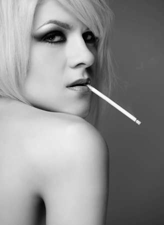 naked blonde: portrait of young topless blonde woman with beautiful body smoking slim cigarette Stock Photo