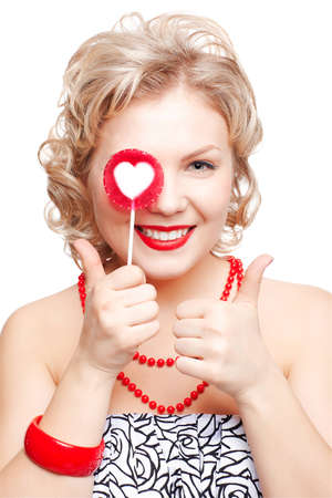 isolated portrait of beautiful happy young blonde size plus woman model with red lollipop with white heart middle showing both thumbs up Stock Photo - 12671223